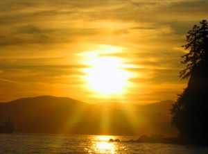 Sun over water and mountains